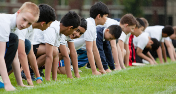 A group of male students crouching at the start line of a grass race track